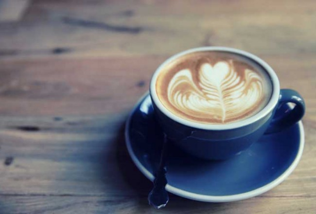latte art in blue cup on wood table