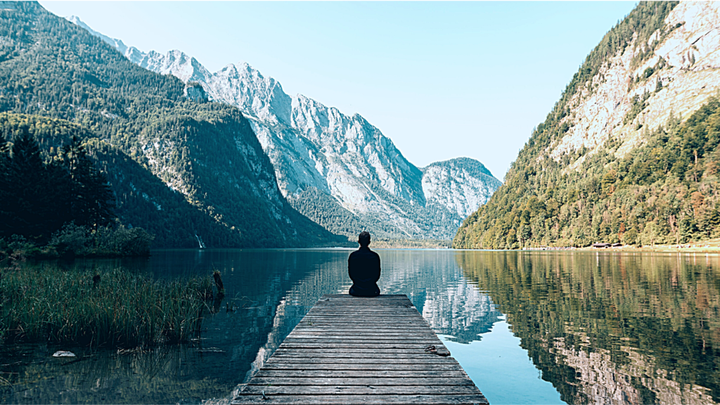 person sitting on dock at lake surrounded by mountains