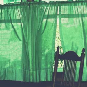 chair beside green curtains