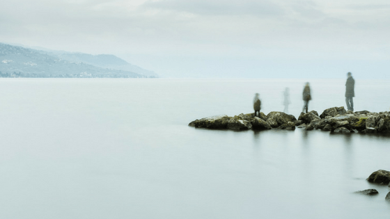 people standing on rock jetty on cloudy day