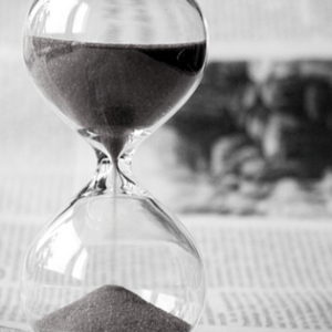 Hourglass standing on an open newspaper