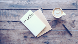 notebook and cafe au lait on a reclaimed wood table