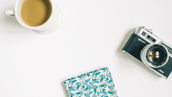 camera, coffee, and patterned notebook