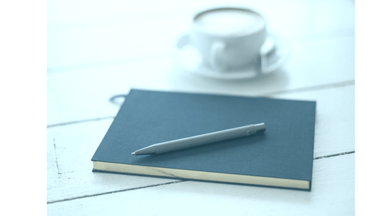 notebook with pen and latte on a whitewashed wood table notebook latte