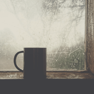 A mug in front of a foggy window.