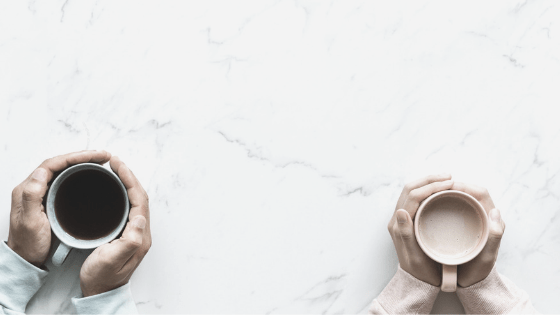 two people's hands clutching 2 coffees on marble table