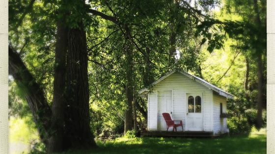 small white cabin in summer woods with red chair