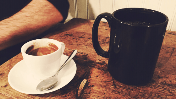black coffee cup and white espresso cup on wood table with man's arm