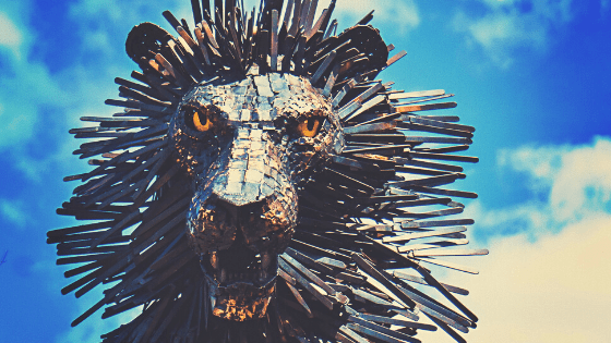 bronze roaring lion statue against a bright cloud-filled sky
