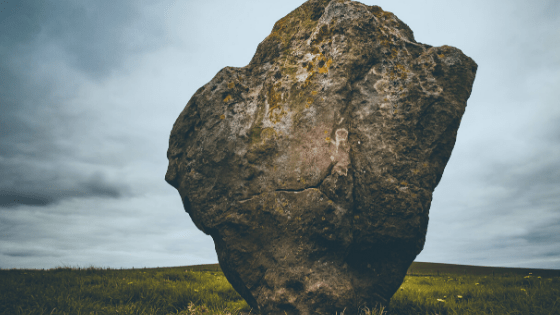 large rock sitting alone in a field on cloudy day