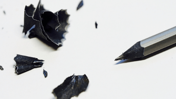 silver graphite pencil with shavings on a white background