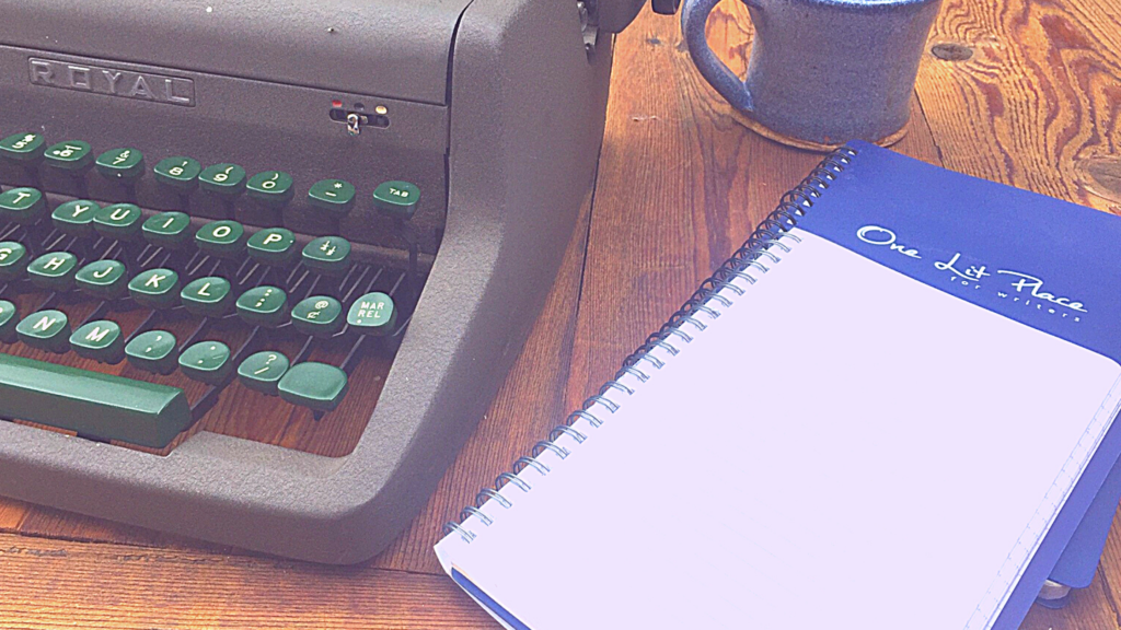 vintage typewriter with blue coffee cup and notebooks