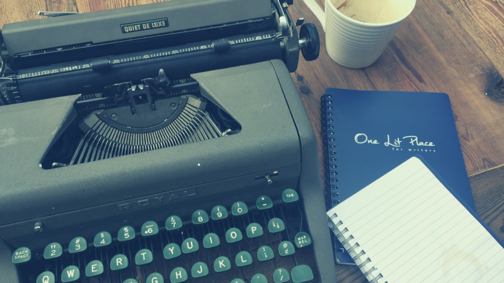 vintage typewriter with One Lit Place notebook and coffee
