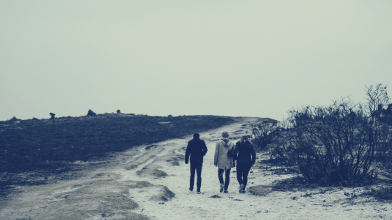three friends walking on lonely beach road
