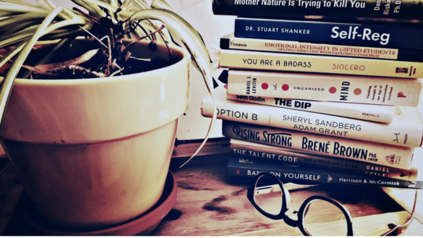 stack of business and self-development books beside yellow potted plant and reading glasses