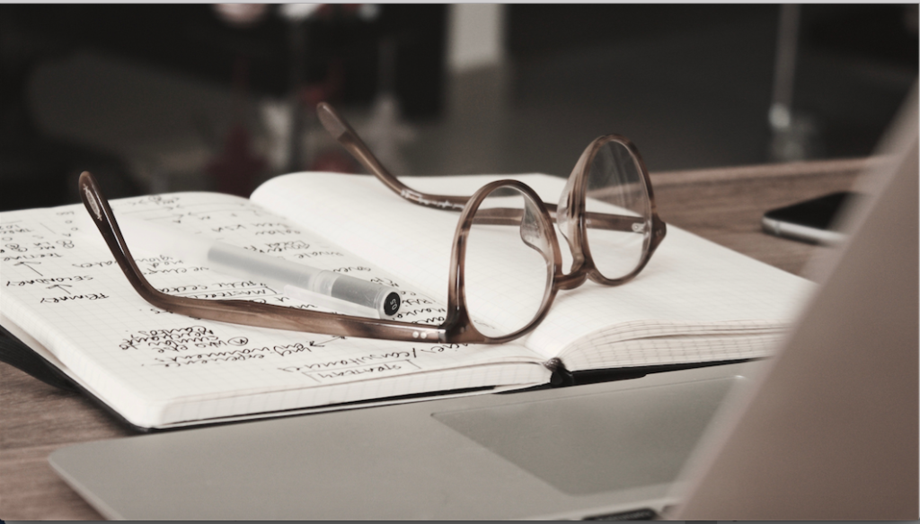 reading glasses on open notebook