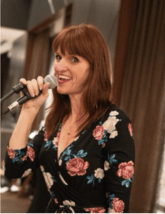 woman with red hair and flower print dress speaking into microphone