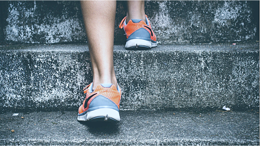 runner in sneakers going up stairs