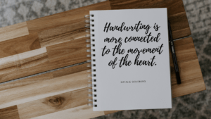 notebook with handwritten script on wood table