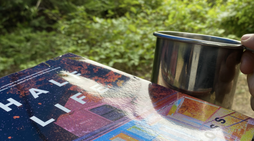 novel krista foss Half Life with metal coffee cup in woods