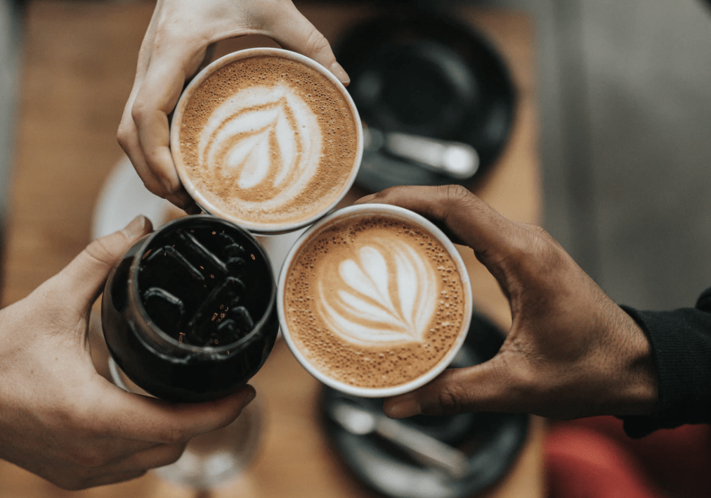 three hands holding coffee cups together